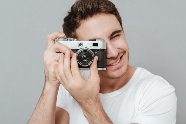 Close-up portret van lachende man foto maken op retro camera. geïsoleerde grijze muur