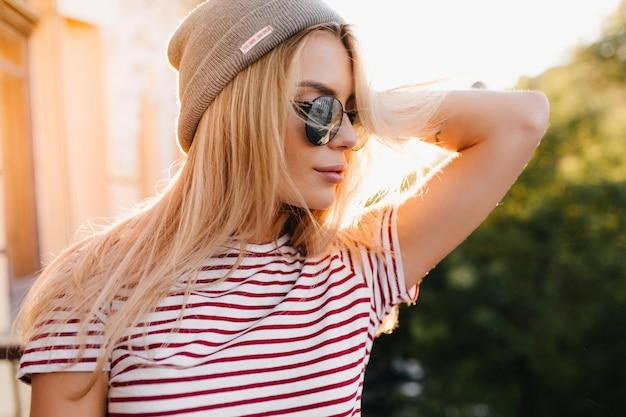 Close-up portret van licht gebruinde blonde vrouw in trendy glanzende zonnebril