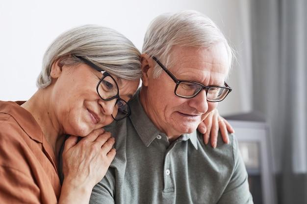 Close-up portret van liefdevol senior paar omarmen thuis terwijl ze samen op de bank zitten en naar het scherm kijken, kopieer ruimte