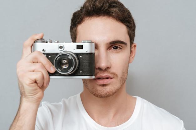 Close-up portret van man foto maken op retro camera. geïsoleerde grijze muur