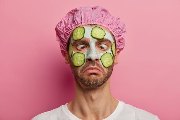 Close-up portret van man met gekruiste ogen, gretig om een perfecte huid te hebben, past een plantaardig gezichtsmasker en komkommers toe, draagt een douchemuts