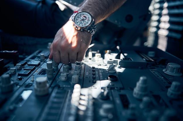 Close-up portret van mannelijke piloot hand op het dashboard paneel duwen en controleren van het systeem van passagiersvliegtuig