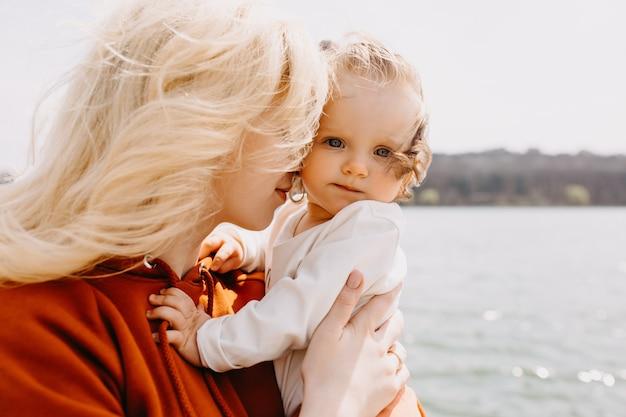 Close-up portret van moeder en klein meisje knuffelen buitenshuis