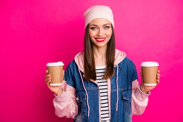 Close-up portret van mooi aantrekkelijk mooi vrij charmant vrolijk vrolijk meisje in handen houden van twee papieren koffiekopjes voor vriend geïsoleerd op heldere, levendige glans levendige roze fuchsia kleur