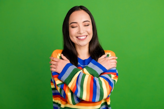 Close-up portret van mooi dromerig vrolijk meisje met gestreepte warme trui die zichzelf omhelst geïsoleerd over levendige groene kleur achtergrond