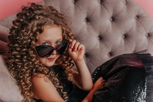 Close-up portret van mooi meisje in zwarte jurk op roze achtergrond dragen van een zonnebril