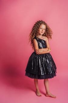 Close-up portret van mooi meisje in zwarte jurk op roze achtergrond in studio glimlachend en poseren?