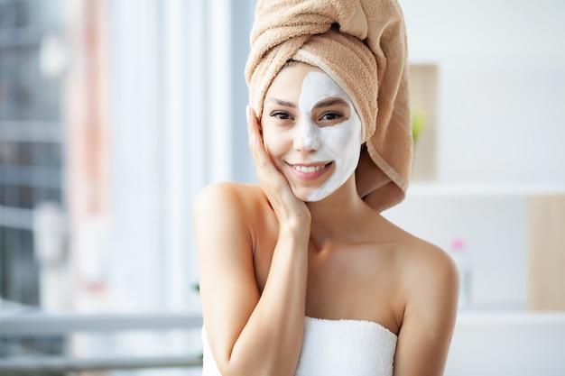 Close-up portret van mooi meisje met een handdoek op haar hoofd gezichtsmasker toe te passen.