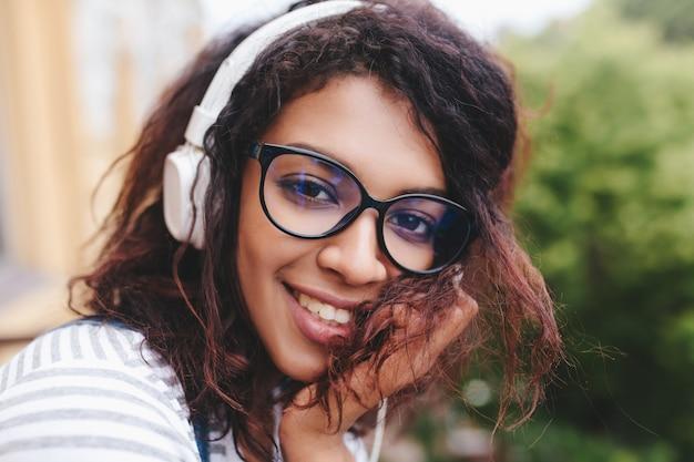 Close-up portret van mooi meisje met grote bruine ogen spelen met krullend haar en muziek luisteren