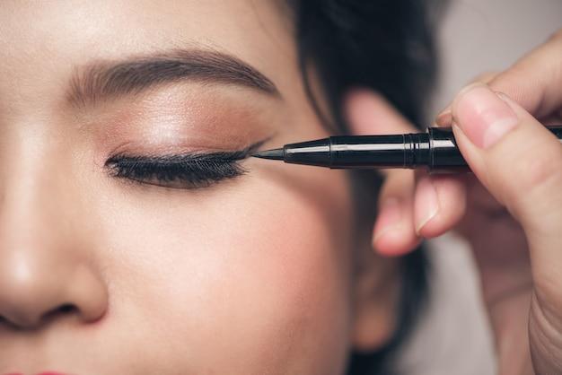 Close-up portret van mooi meisje wat betreft zwarte eyeliner aan haar ooglid met gesloten ogen.
