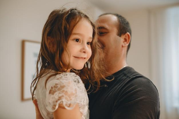Close-up portret van mooi meisje wegkijken glimlachend terwijl wordt vastgehouden door haar vader thuis.