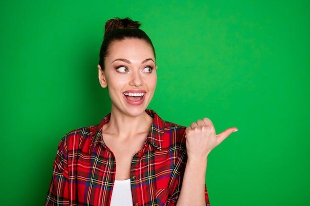 Close-up portret van mooi uitziende aantrekkelijke vrij blij vrolijk vrolijk meisje in ingecheckte shirt weergegeven: advies advertentie oplossing geïsoleerd op heldere levendige glans levendige groene kleur achtergrond