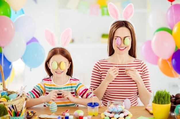 Close-up portret van mooie aantrekkelijke funky creatieve vrolijke meisjes kleine pre-tiener zusje bunny oren dragen die betrekking hebben op ogen met decoratieve eieren in wit licht interieur kamer huis