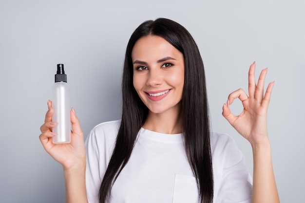 Close-up portret van mooie aantrekkelijke vrolijke vrolijke straighthaired meisje in handen houden spray wassen schoonmaken handen gezondheid quarantaine weergegeven: oksign geïsoleerd op lichtgrijze pastel kleur achtergrond