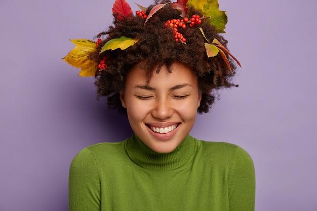 Close-up portret van mooie afro-amerikaanse vrouw lacht hardop, heeft brede brede glimlach, houdt de ogen gesloten van plezier, draagt herfstbladeren vast in haar in goed humeur
