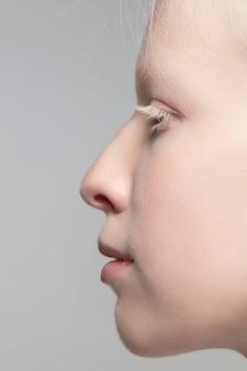 Close-up portret van mooie albino vrouw geïsoleerd op studio achtergrond. . details.