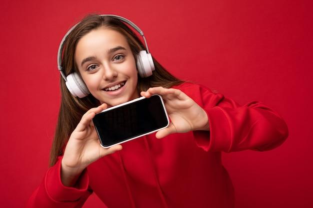 Close-up portret van mooie brunette meisje dragen rode hoodie geïsoleerd op rode achtergrond holding