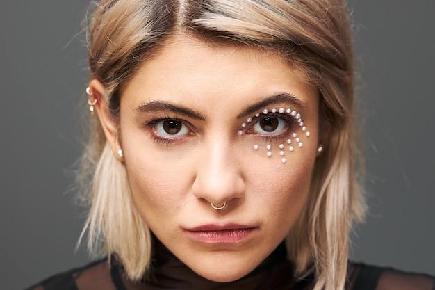Close-up portret van mooie charmante jonge blonde vrouwelijke model met kort geverfd haar naar rechts staren, met mysterieuze intentie blik, zwarte jurk, gezicht piercing en glamoureuze make-up dragen