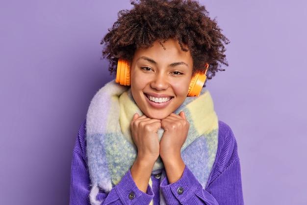 Close-up portret van mooie donkere huid duizendjarige meisje houdt handen onder kin glimlacht breed geniet vrije tijd draagt winterkleren luistert aangename muziek.