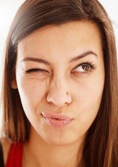 Close-up portret van mooie jonge blanke lachende vrouw knipogen en wegkijken.