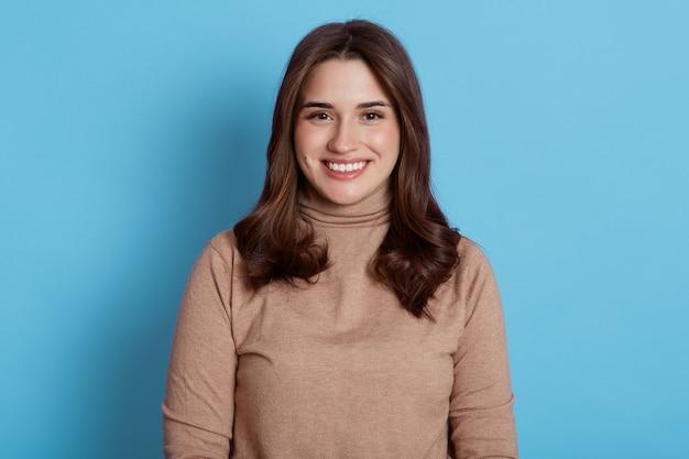 Close-up portret van mooie jonge europese vrouw model met donker haar kijken met charmante schattige glimlach terwijl poseren tegen blauwe muur, aantrekkelijke gelukkige vrouw positief uitdrukken.