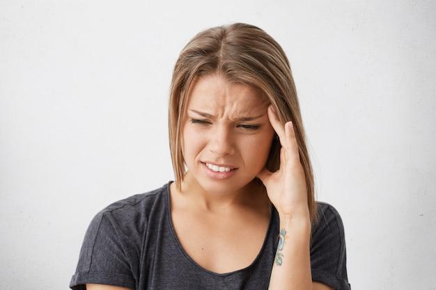 Close-up portret van mooie jonge vrouw met bob kapsel hand in hand op haar slaap, kronkelend van pijn als haar hoofd pijn doet, zich ziek en gestrest voelen. hoofdpijn, migraine, ziekte en ziekte