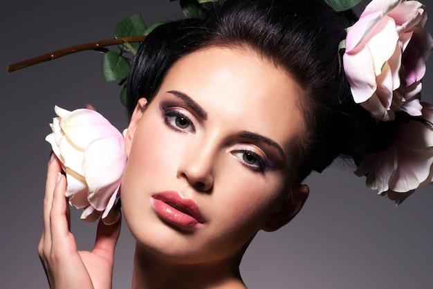 Close-up portret van mooie jonge vrouw met roze bloemen in haar - op een grijze achtergrond