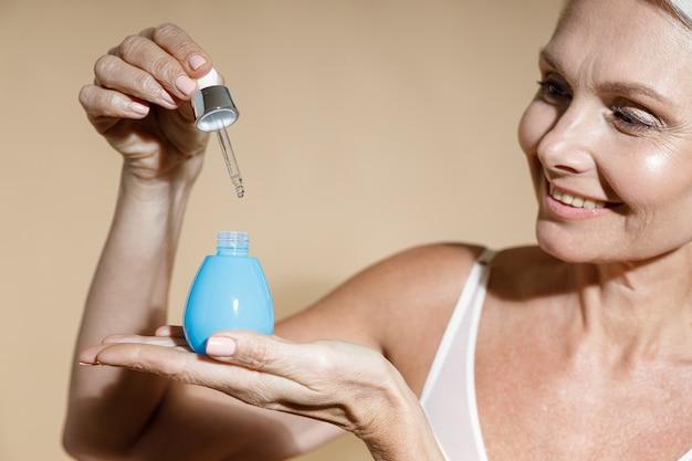 Close-up portret van mooie lachende volwassen vrouw met fles serum en pipet zuur voor