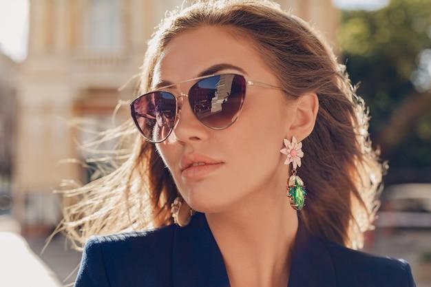 Close-up portret van mooie vrouw gekleed in stijlvolle blauwe jas wandelen in herfst zonnige straat elegante zonnebril en oorbellen dragen