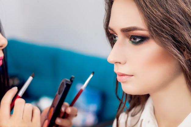 Close-up portret van mooie vrouw krijgt professionele make-up met borstel