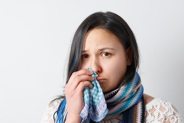 Close-up portret van mooie vrouw niest en hoest, gebruikt weefsel, wrijft over de neus, heeft ernstige verkoudheid