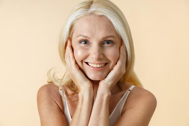 Close-up portret van natuurlijke rijpe vrouw met blond haar in wit ondergoed glimlachend in de camera