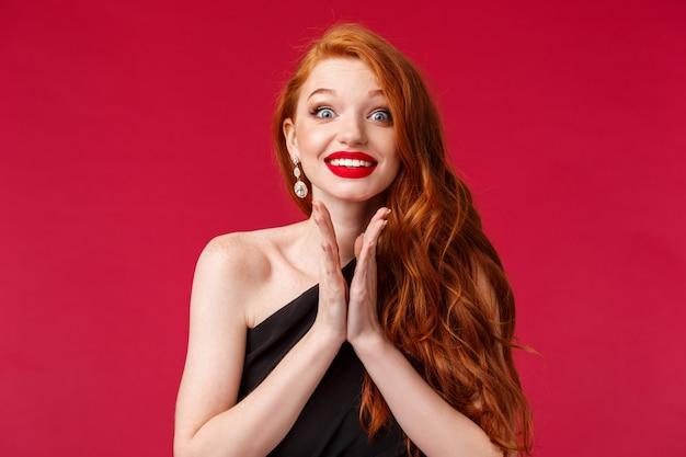 Close-up portret van opgewonden en gretige jonge prachtige roodharige vrouw handen klappen anticiperen op prestaties, hoopvol glimlachend, in afwachting van kunstenaar komen op het podium kan niet wachten om hem te horen, rode muur