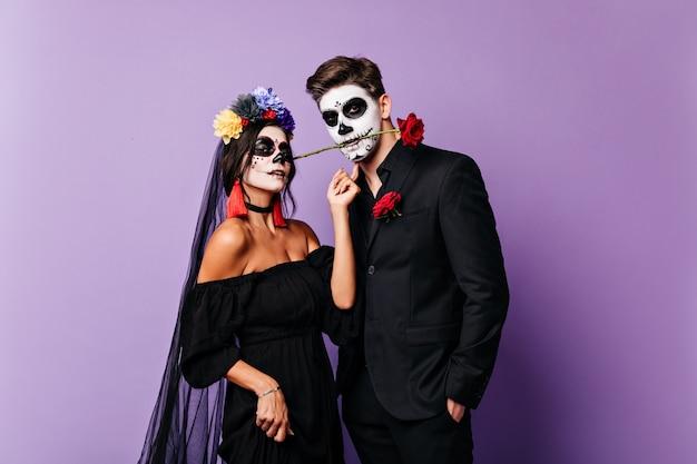 Close-up portret van paar liefhebbers in feestelijke carnaval kostuums poseren op paarse achtergrond. gepassioneerde mexicaanse man houdt roos tussen zijn tanden terwijl zijn bruid in de camera kijkt.