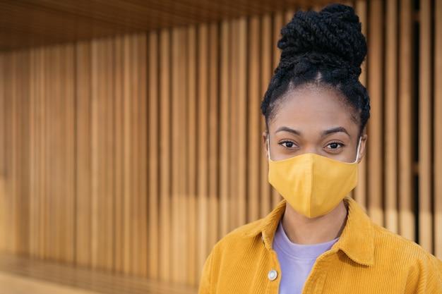 Close-up portret van peinzende afro-amerikaanse vrouw die een beschermend gezichtsmasker draagt en naar de camera kijkt