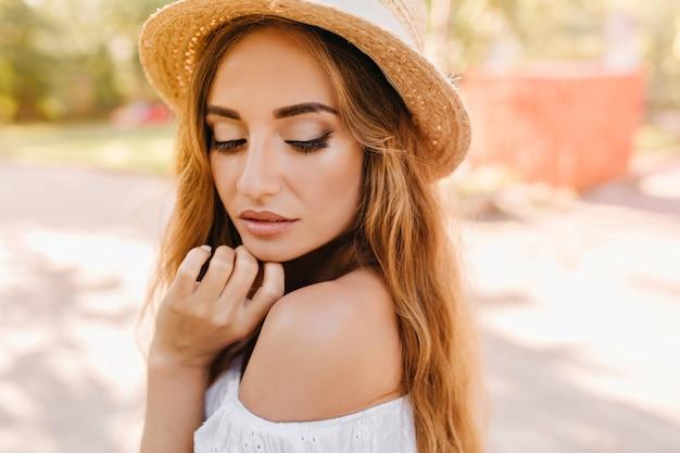 Close-up portret van peinzende vrouw met licht gebruinde huid en trendy naakt make-up poseren met gesloten ogen. buiten foto van dame in vintage hoed kin aan te raken en naar beneden te kijken.