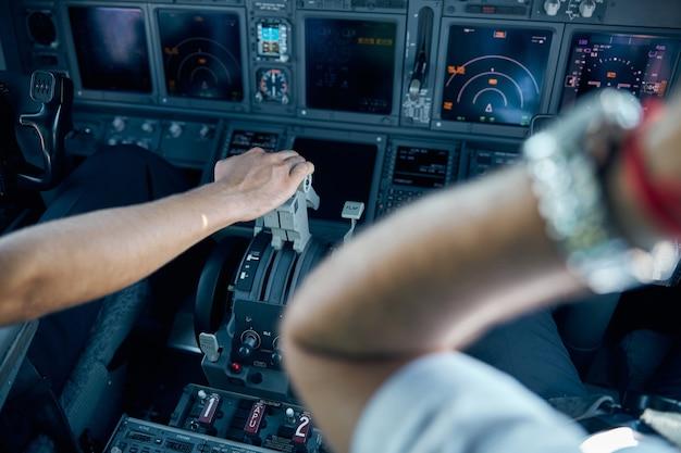 Close-up portret van piloot hand op het gaspedaal in civiel vliegtuig