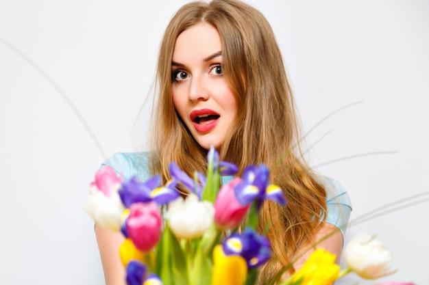 Close-up portret van positieve blonde vrouw met lente bloemboeket, lange haren, verrassing aanwezig voor u, focus op mooi gezicht.