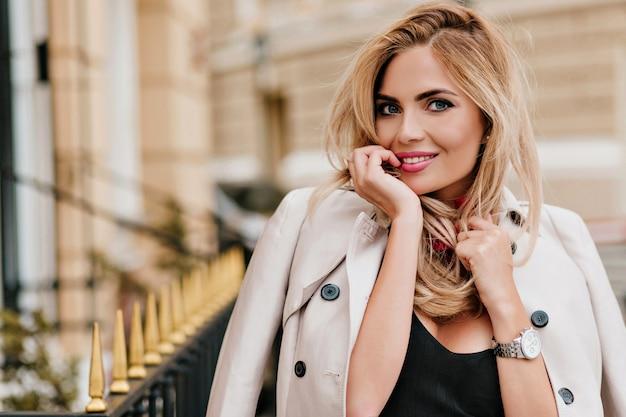Close-up portret van prachtig europees meisje speels poseren in nieuwe beige jas