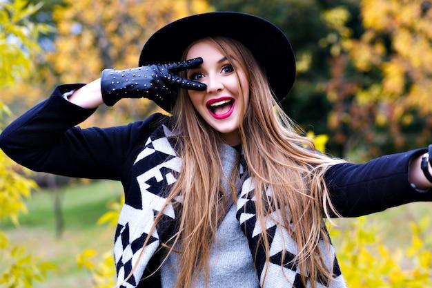 Close-up portret van prachtige dame in zwarte hoed gek rond tijdens herfst fotoshoot. grappige jonge dame in elegante handschoenen tijd doorbrengen in park in september dag.