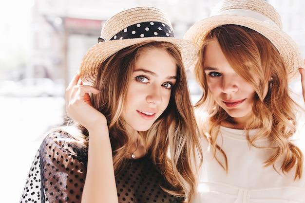 Close-up portret van prachtige krullende meisjes met glanzend haar poseren samen met groot raam