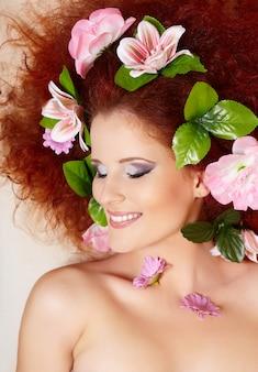 Close-up portret van prachtige lachende roodharige gember vrouw gezicht met kleurrijke bloemen in haar in porofile