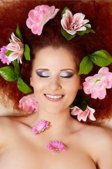 Close-up portret van prachtige lachende roodharige gember vrouw gezicht met kleurrijke bloemen in haar