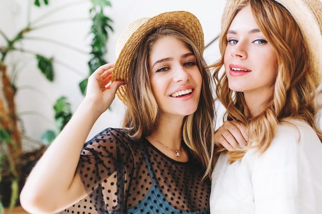 Close-up portret van prachtige meisjes met krullend haar poseren in hoeden voor muur met plant