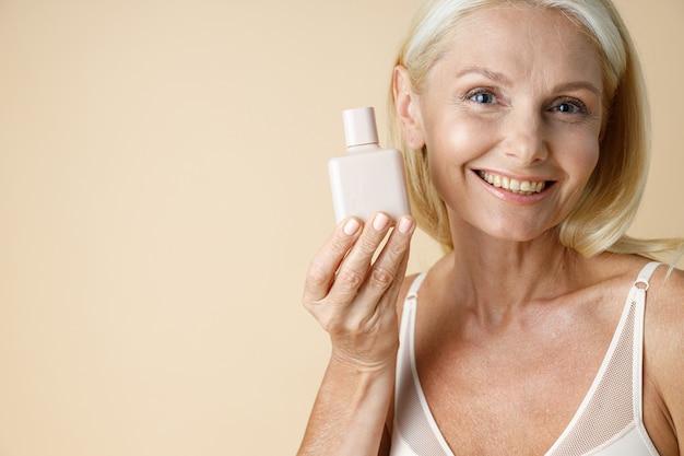 Close-up portret van prachtige rijpe blonde vrouw in ondergoed glimlachend in de camera met wit