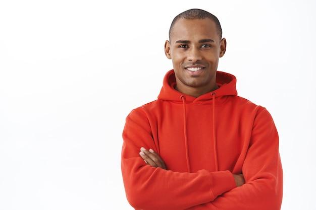 Close-up portret van professionele, succesvolle jonge afro-amerikaanse man in rode hoodie, kruis armen borst arms