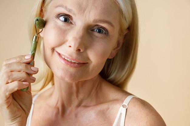 Close-up portret van rijpe blonde vrouw met gloeiende huid glimlachend in de camera tijdens het gebruik van jade