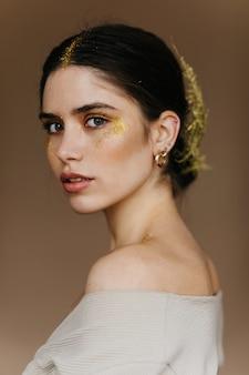 Close-up portret van romantische jonge vrouw. debonair mooi meisje met gouden accessoires poseren op donkere muur.