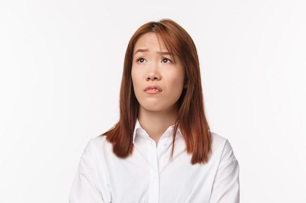 Close-up portret van sceptisch jong aziatisch meisje grijnzende afkeer en veroordelend links kijkend, wenkbrauw opgetrokken verrast en niet onder de indruk van iets onaangenaams, witte muur staan