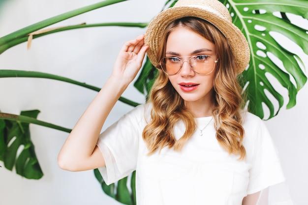 Close-up portret van schattige blonde vrouw haar strooien hoed met sluwe glimlach aan te raken